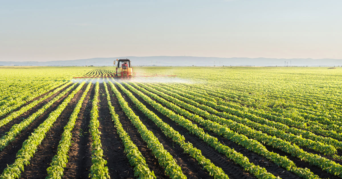 Tractor spraying soybean field with pesticides